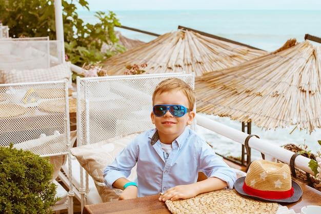 Jongen in restaurant op zee strand, niemand anders, witte stoelen en stro parasols
