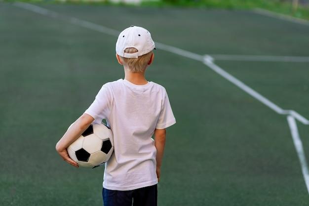 Jongen in sportkleren, zittend op een groen gazon op een voetbalveld met een voetbal