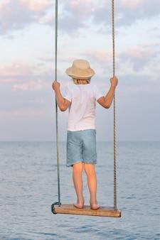 Jongen in strooien hoed staande op een schommel touw en kijkt uit op zee. verticaal frame.