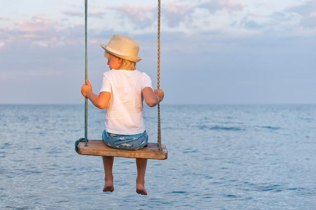 Jongen in strooien hoed zittend op een schommel touw op zee achtergrond. achteraanzicht.