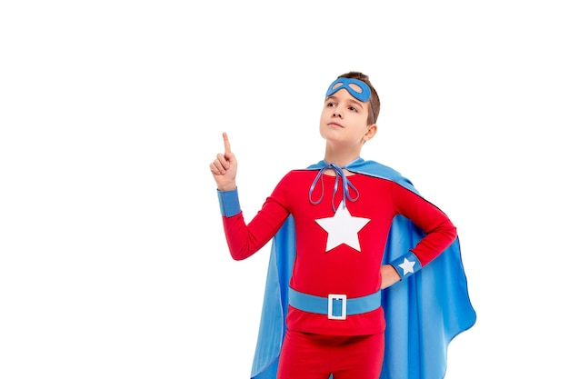 Jongen in superheld kostuum hand in hand op taille en wijzend op lege ruimte op wit