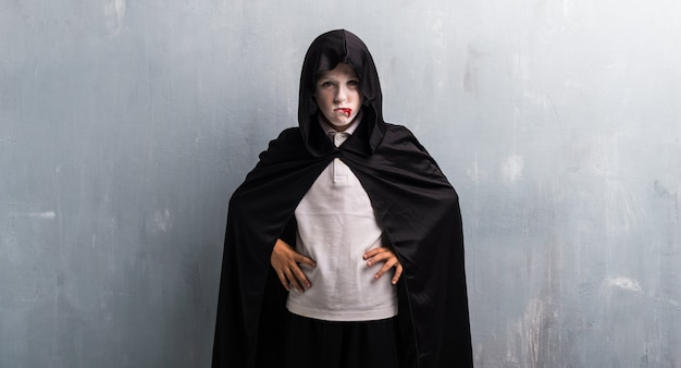 Jongen in vampierkostuum voor halloween-vakantie die met wapens bij heup stellen