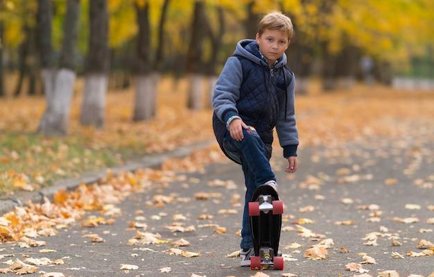 Jongen in warme jas doet skateboardtruc in park in de herfst, geschoten in volledige lengte voorportret met kopie ruimte aan de linkerkant