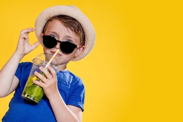 Jongen in zomeroutfit die een zonnebril draagt en geniet terwijl hij een mojito-cocktail drinkt. poseren op de gele achtergrond.
