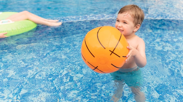 Jongen in zwembad met bal