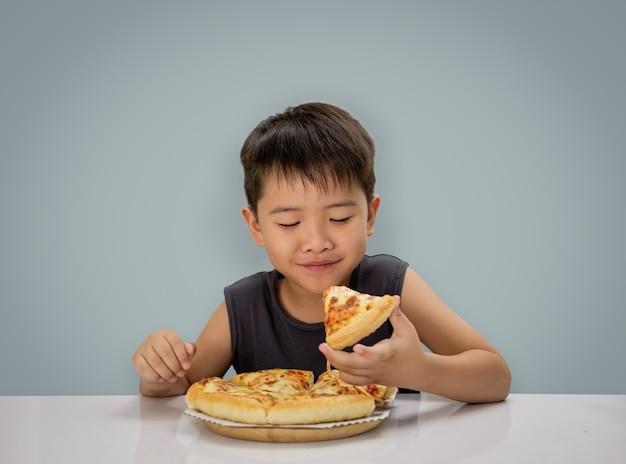 Jongen is blij pizza eten met een hete kaas smelten uitgerekt op een houten plaat