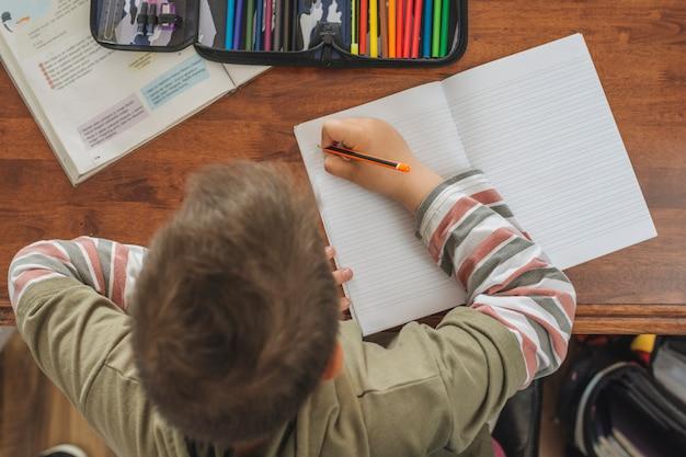 Jongen is zijn huiswerk aan het doen