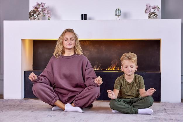 Jongen jaar oud maakt yoga-oefeningen met moeder thuis