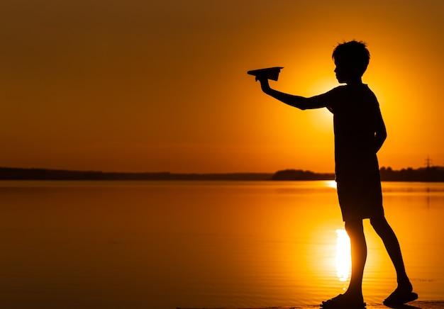 Jongen jongen houdt een papieren vliegtuigje in zijn hand bij de rivier bij prachtige oranje zonsondergang in de zomer.