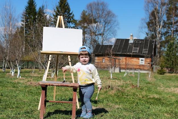 Jongen jongen kunstenaar schildersezel borstel buiten
