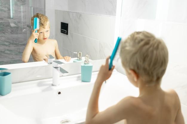 Jongen kamt zijn haar voor de spiegel in de ochtend in het bad, hygiëne in de ochtend