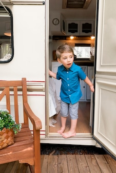Jongen kijkt achter de deur van zijn caravan