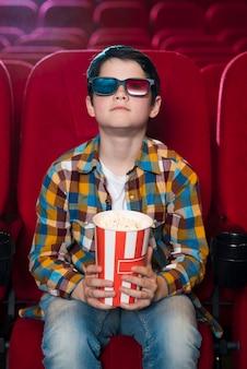 Jongen kijkt naar film in de bioscoop