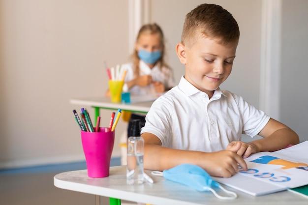 Jongen kijkt naar zijn boek in de klas