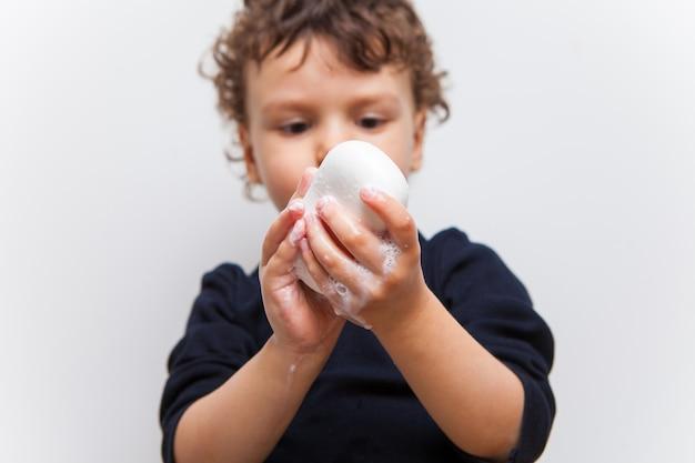 Jongen, kind zijn handen inzepen met zeep close-up