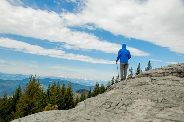 Jongen klimmen stevige enorme rotsen met palen