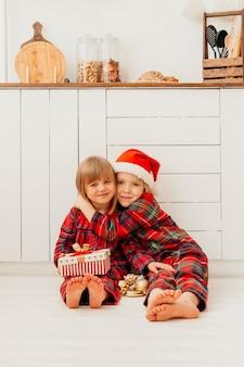 Jongen knuffelen zijn zus op eerste kerstdag