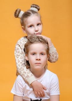 Jongen knuffels een meisje, broer en zus op geel