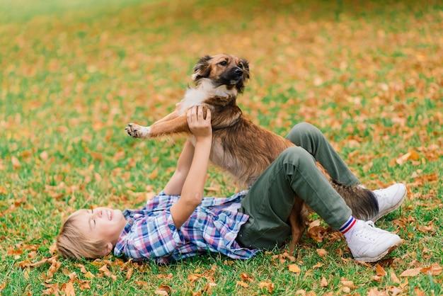 Jongen knuffelt hond en speelt in de herfst, stadspark