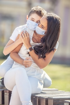 Jongen knuffelt zijn moeder vanaf de achterkant, houdt handen vast terwijl hij buiten is, met gezichtsmaskers op.