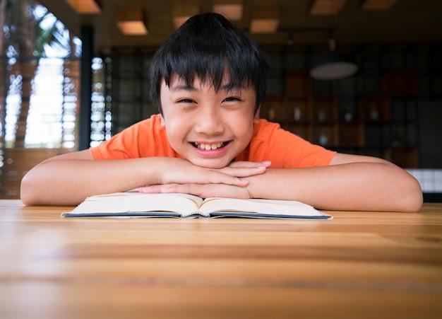 Jongen lachend met een boek op houten tafel. thuis leren
