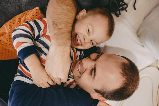 Jongen lacht en heeft vreugde met zijn vader