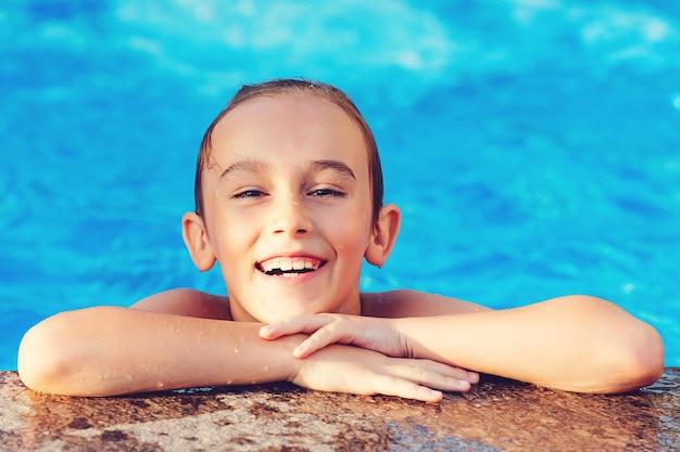 Jongen lacht en rust tijdens vakanties. leuke jongen die plezier heeft in het zwembad.