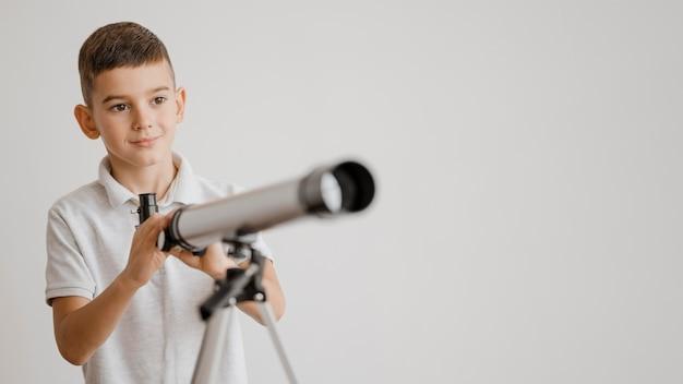 Jongen leert hoe hij een telescoop met kopie ruimte moet gebruiken