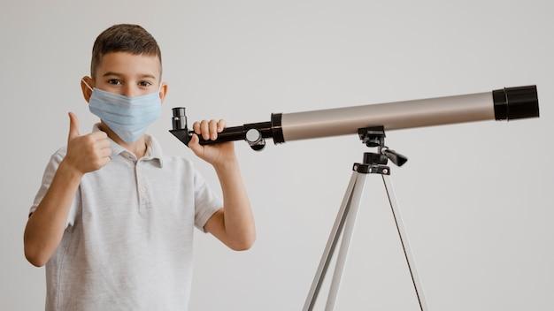 Jongen leert hoe hij een telescoop moet gebruiken