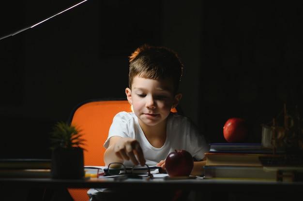 Jongen leert lessen in de thuisomgeving aan tafel in het licht van een tafellamp.