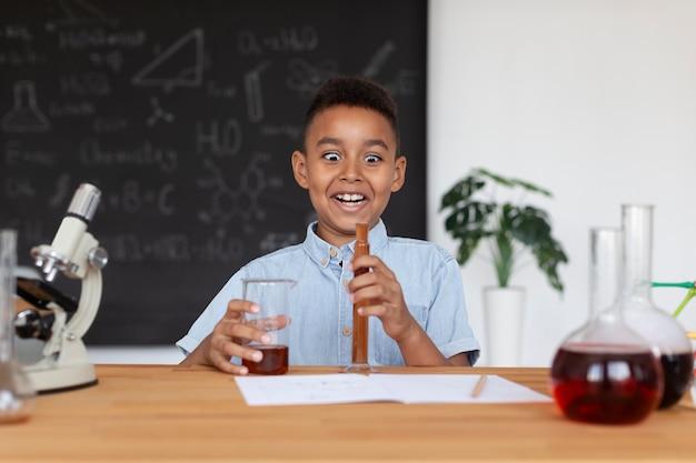 Jongen leert meer over scheikunde in de klas