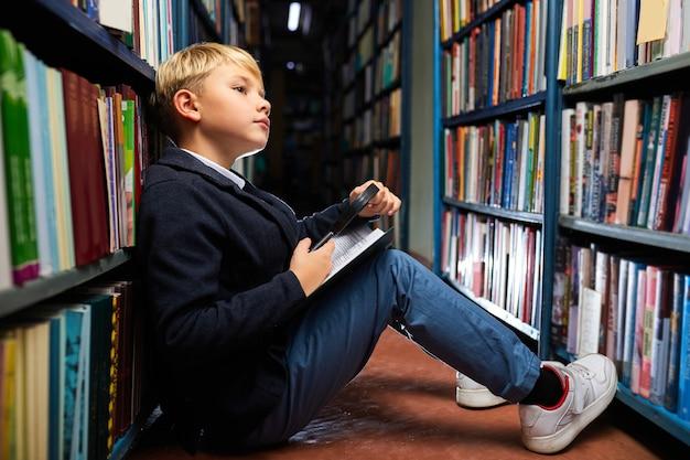 Jongen leest zorgvuldig elk woord in het boek met behulp van een vergrootglas, zittend op de vloer tussen de planken in de bibliotheek