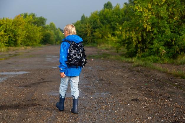 Jongen loopt door de plassen in rubberen laarzen en met een rugzak