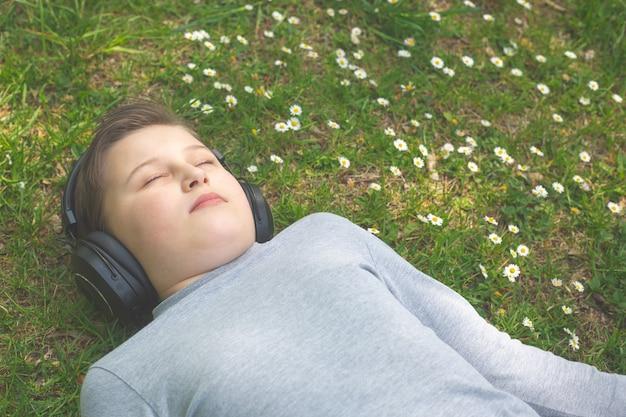 Jongen luistert of geniet van muziek buiten of parkeert met grote koptelefoon