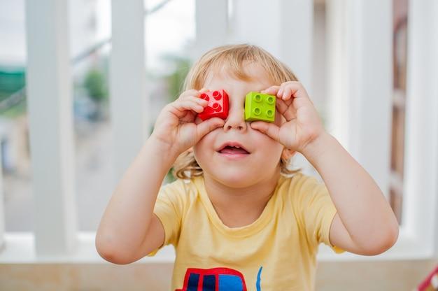 Jongen maakt ogen van kleurrijke kinderblokken. schattige kleine jongen jongen met bril spelen met veel kleurrijke plastic blokken binnen. bevordering van vaardigheden en creativiteit