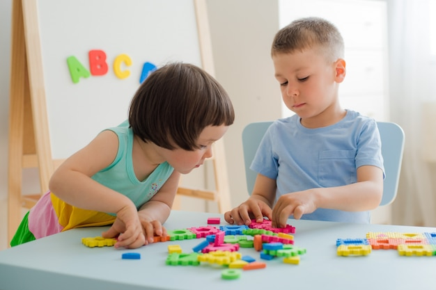 Jongen meisje verzamelt zachte puzzel aan tafel. broer zus veel plezier samen kamer spelen.
