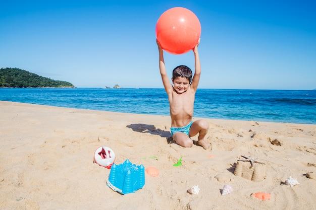 Jongen met bal op het strand