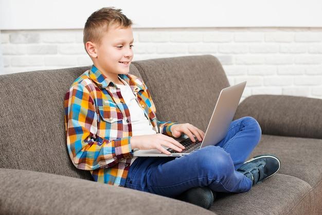 Jongen met behulp van laptop op de bank