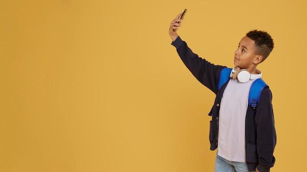 Jongen met blauwe rugzak die een zelffoto-exemplaarruimte neemt