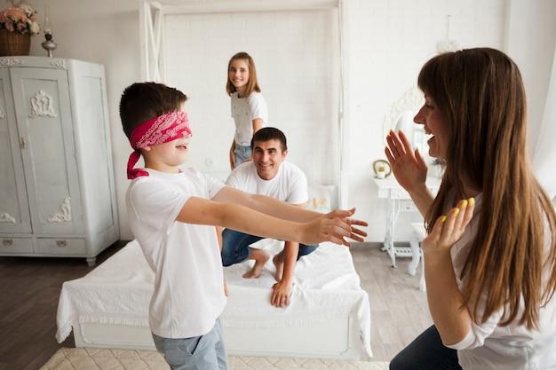Jongen met blinddoek betrapt moeder tijdens het spelen van blinde buff
