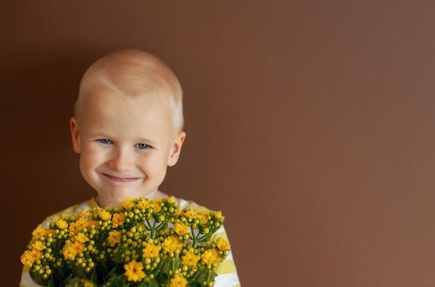 Jongen met bloemen. lachend kind met een boeket bloemen.