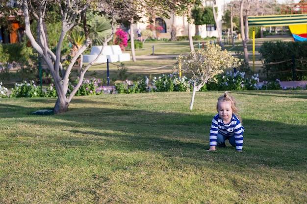 Jongen met blond haar kruipt op groen gras. kind in blauwe kleren spelen op zonnige dag. gelukkig kindertijdconcept. activiteit, ervaring, leren. zomervakantie, avontuur, ontdekking.