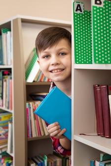 Jongen met boek tussen planken