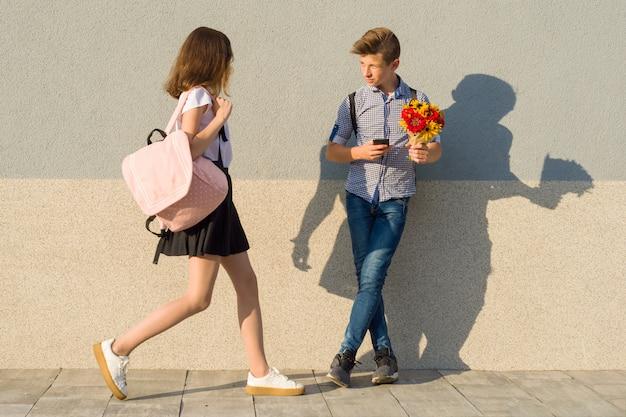 Jongen met boeket bloemen en meisje