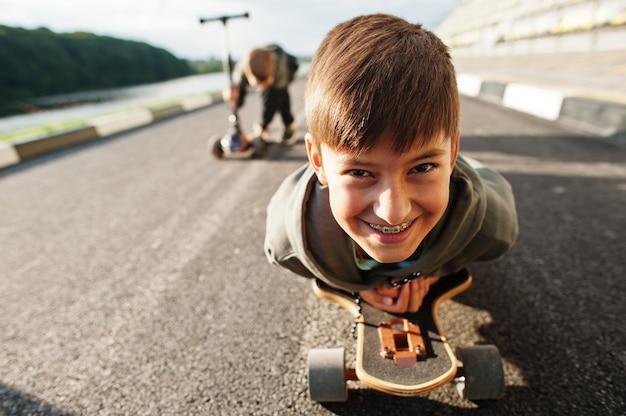 Jongen met bretels liggend op een skateboard, close-up portret.