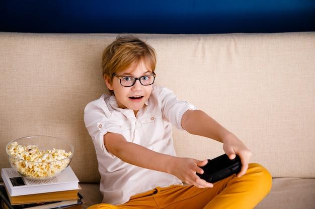 Jongen met bril speelt videogames houdt een gamepad vast en eet popcorn in plaats van lessen te leren