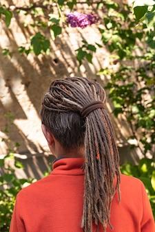 Jongen met creatieve mode gevlochten dreadlocks kapsel oranje trui dragen