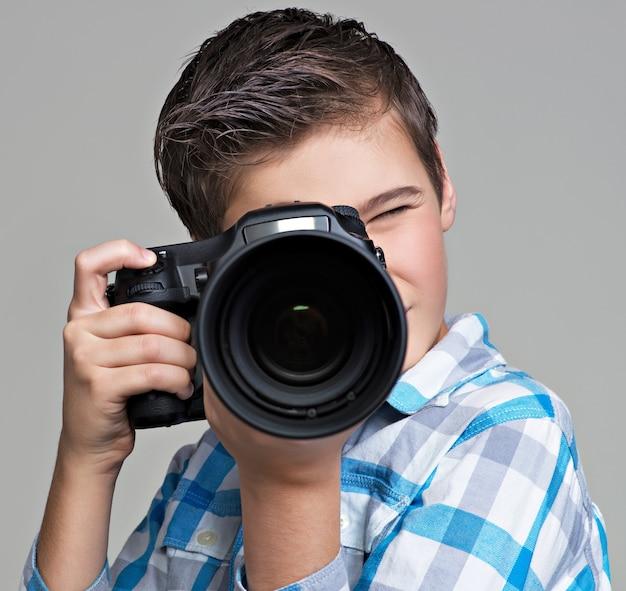 Jongen met dslr camera fotograferen. tienerjongen met camera die foto's maakt.