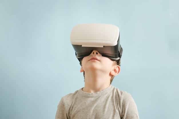 Jongen met een bril van virtual reality. blauwe achtergrond
