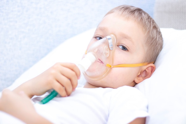 Jongen met een inhalatormasker - ademhalingsproblemen bij astma. een jongen met een inhalatormasker ligt in bed en ademt adrenaline in. gezondheidszorgconcept en ziek kind, coronavirus, bronchitis, longontsteking